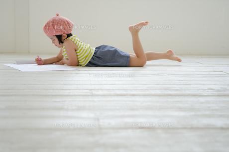 床に寝そべって絵を描く女の子 FYI01077361