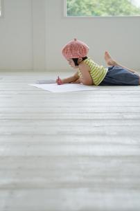 床に寝そべって絵を描く女の子 FYI01077365