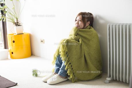 緑の毛布にくるまって座る女性 FYI01077366