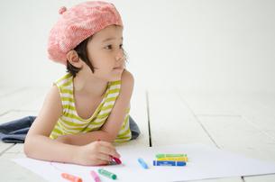 床に寝そべって絵を描く女の子 FYI01077368