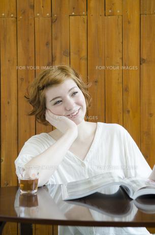 机に頬杖を付いて微笑むハーフの女性 FYI01077369