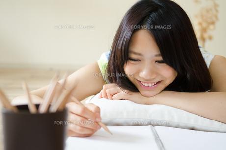 ノートに何かを書きながら笑う女性 FYI01077370