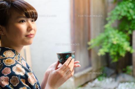 お茶の入った湯のみを持つ着物姿の女性 FYI01077372