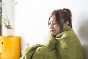 緑の毛布にくるまる女性 FYI01077378
