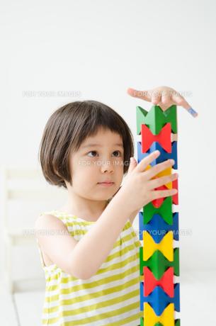 知育おもちゃで真剣に遊ぶ女の子 FYI01077381