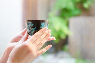 お茶の入った湯のみを持つ着物姿の女性の手 FYI01077383