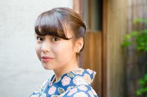 日本家屋をバックに着物姿の女性 FYI01077387