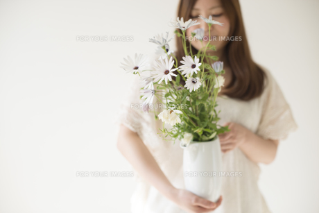 ポットに入った白いデイジーを持つ女性 FYI01077392