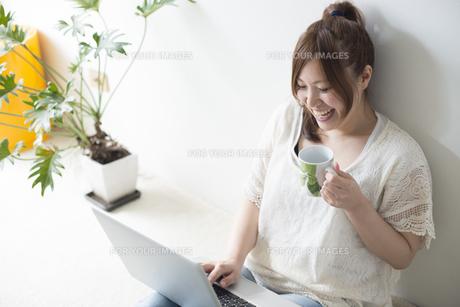カップを片手にノートパソコンを操作する女性 FYI01077395