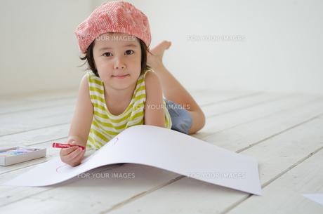 床に寝そべって絵を描く女の子 FYI01077396