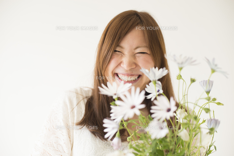 白いデイジーを持って笑う女性 FYI01077398