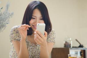 部屋の中でスマートフォンを操作する女性 FYI01077399