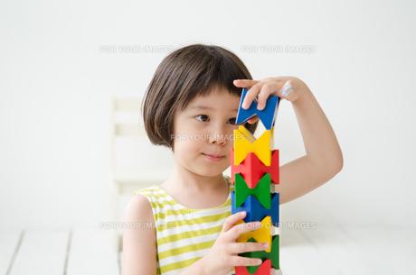 知育おもちゃで真剣に遊ぶ女の子 FYI01077405