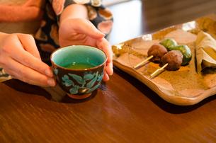 机にある和菓子と湯のみに添えられた着物姿の女性の手 FYI01077407