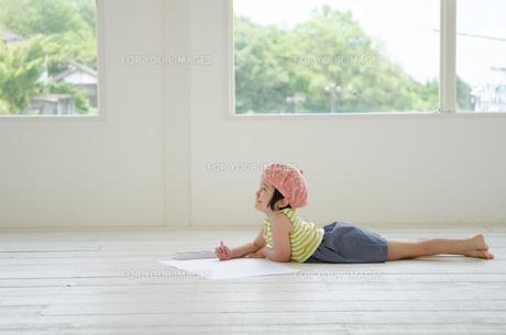 床に寝そべって絵を描く女の子 FYI01077408