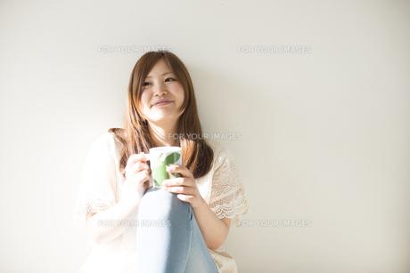 カップを持って微笑む女性 FYI01077410