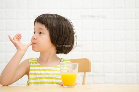 イスに座って親指を舐める女の子 FYI01077414