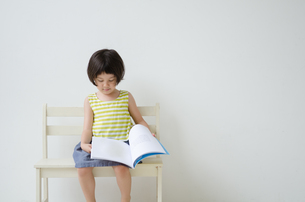 ベンチに座って絵本をめくる女の子 FYI01077424