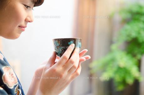 お茶の入った湯のみを持つ着物姿の女性 FYI01077429