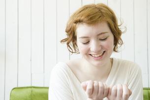 室内で自分の爪を見ているハーフの女性 FYI01077440