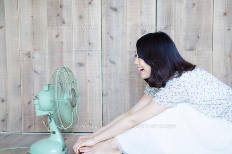 扇風機に向かって声を出している女性 FYI01077441