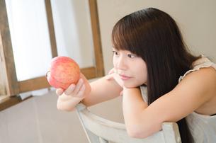 りんごを眺めている女性 FYI01077448