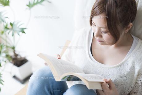 イスに座って本を読む女性 FYI01077462