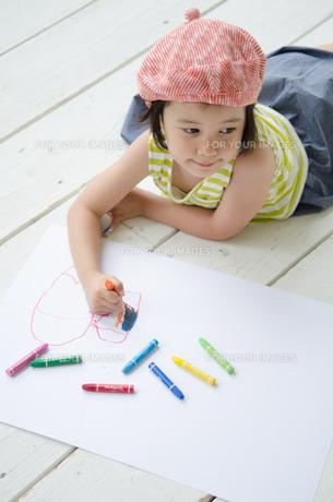 床に寝そべって絵を描く女の子 FYI01077473