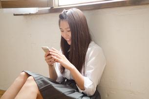 床に座って携帯電話を見ている制服姿の女性 FYI01077475