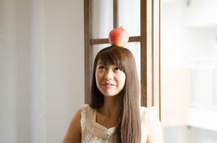 りんごを頭の上に乗せている女性 FYI01077481