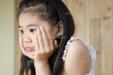 頬杖を付いて考えている女の子 FYI01077497
