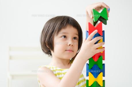 知育おもちゃで真剣に遊ぶ女の子 FYI01077507