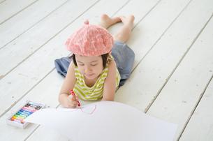 床に寝そべって絵を描く女の子 FYI01077514