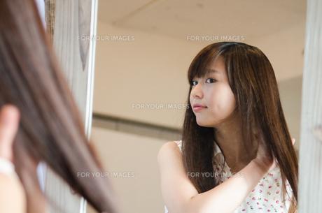 鏡の前で髪をセットする女性 FYI01077519