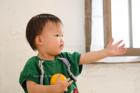オレンジを持って手を伸ばしている女の子 FYI01077525