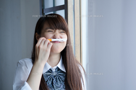 ペンを鼻の下に挟む制服姿の女性 FYI01077544