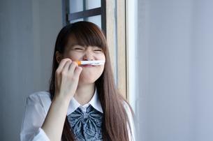 ペンを鼻の下に挟む制服姿の女性の素材 [FYI01077544]