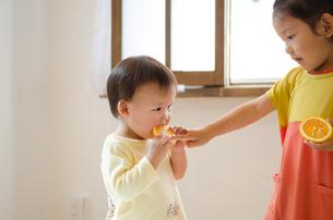 オレンジを食べている姉妹 FYI01077551