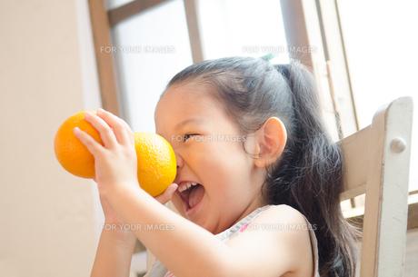 オレンジを持ってふざけている女の子 FYI01077554