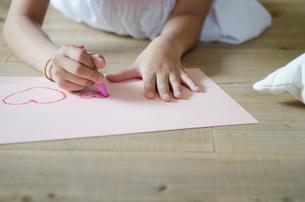 床の上でお絵描きをしている子供の手元 FYI01077559