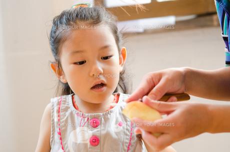 包丁でりんごを切っている手元を見ている女の子 FYI01077563