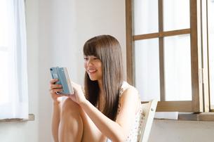 イスに座ってスマートフォンを操作する女性 FYI01077576