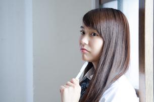 ペンを持って考えている制服姿の女性 FYI01077581