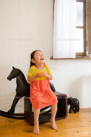オレンジを持って笑っている女の子 FYI01077585