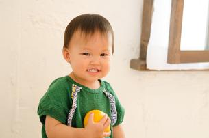 オレンジを持って笑っている女の子 FYI01077591