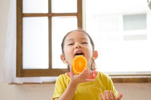 オレンジを食べている女の子 FYI01077612