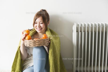 緑の毛布にくるまってみかんを眺める女性 FYI01077630