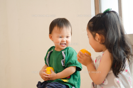 オレンジを持って笑っている姉妹 FYI01077639