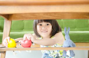 机の下で遊んでいる女の子 FYI01077640
