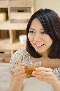 お茶の入ったグラスを持って笑う女性 FYI01077647